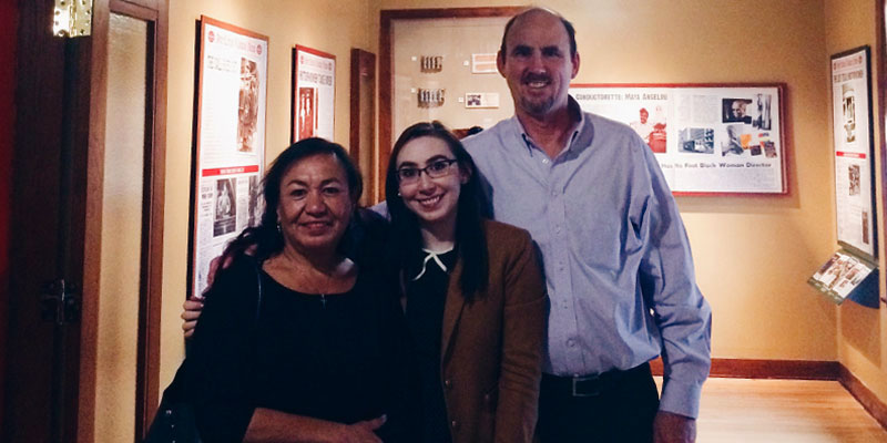 Jessica Woods poses with parents in front of Vital to Victory exhibit