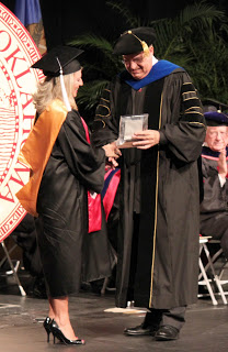 CLS student Andrea Hood receives the George Henderson Award at graduation
