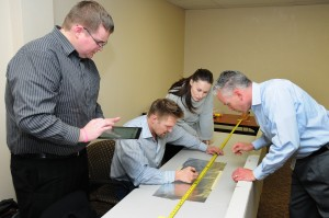 (left to right) Bryan Wilson, Ken Rios, Candice Hopcus, and Chap Williams work together in a classroom exercise with the catapult to use statistical tools to assess process variability and control.