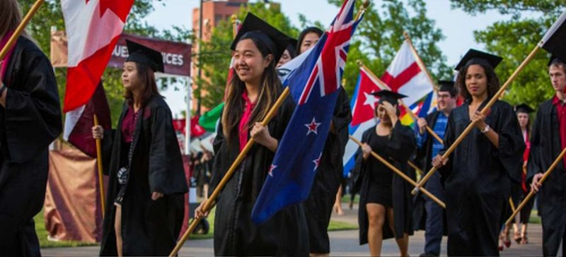 Students carrying flags at graduation