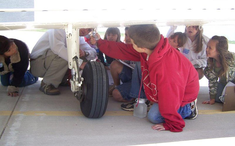 Day camp students inspecting an airplane