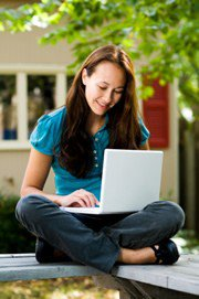 female student typing on a laptop outdoors