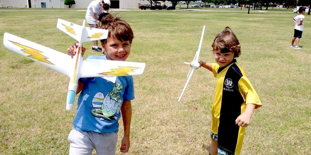 Two young campers posing with their decorated model airplanes.